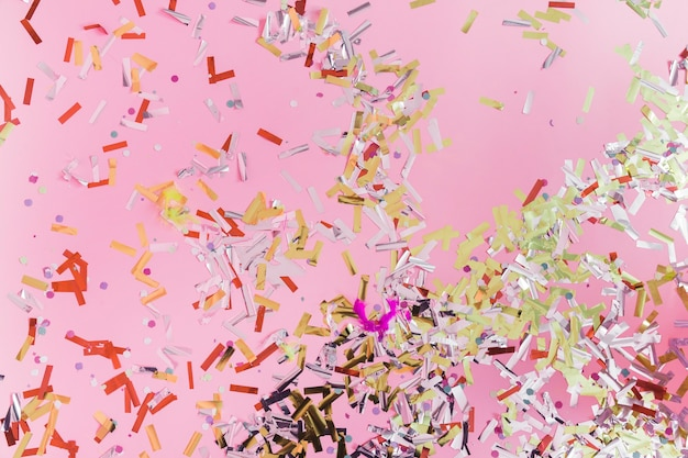 Erhöhte ansicht von bunten konfettis auf rosa hintergrund