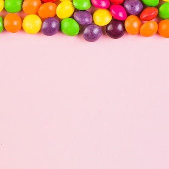 Erhöhte ansicht von bunten süßigkeiten an der spitze des rosa hintergrundes