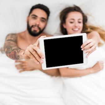 Erhöhte ansicht von den jungen paaren, die auf dem bett hält digitale tablette liegen