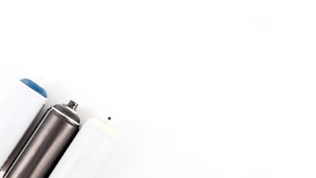 Erhöhte ansicht von den metallischen spraydosen in folge lokalisiert auf weißem hintergrund