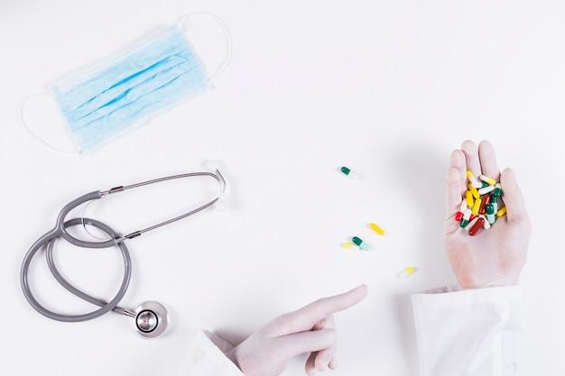 Erhöhte ansicht von doktor zeigend auf die bunten kapseln, die in seiner hand mit stethoskop und maske halten