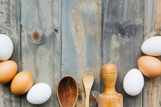 Erhöhte ansicht von eiern mit nudelholz und löffel auf hölzernem hintergrund