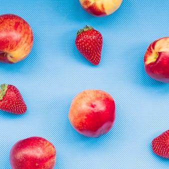 Erhöhte ansicht von erdbeeren und von apfel auf blauem hintergrund
