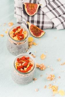 Erhöhte ansicht von feigenscheiben; tuch und chia-smoothie in transparentem glas