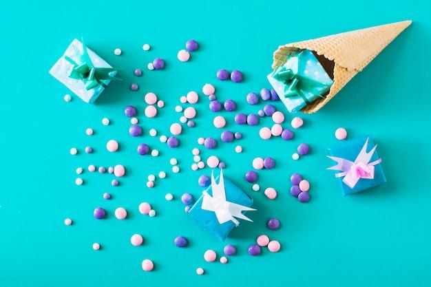 Erhöhte ansicht von geschenkboxen; süßigkeiten und waffeleis auf grünem hintergrund