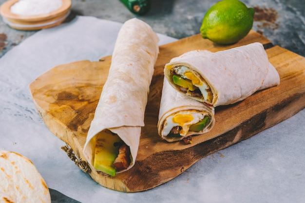 Erhöhte ansicht von geschmückten köstlichen mexikanischen nachos in der platte mit verpackungstacos auf schneidebrett