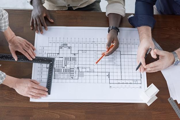 Erhöhte ansicht von ingenieuren, die mit bleistift zeichnen und mit lineal messen, die sie am tisch über blaupausen arbeiten