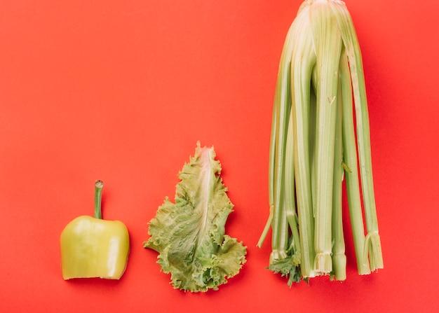 Erhöhte ansicht von mangold salat und grüne paprika auf rotem hintergrund