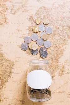Erhöhte ansicht von münzen über dem offenen glas auf weltkarte