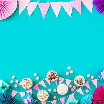 Erhöhte ansicht von muffins mit partyzubehör auf grünem hintergrund