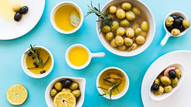 Erhöhte ansicht von olivenöl im unterschiedlichen behälter auf blauem hintergrund