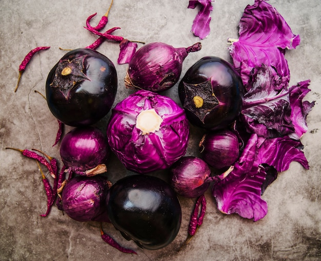 Erhöhte ansicht von purpurkohl; aubergine; zwiebel und rote chilischoten am boden