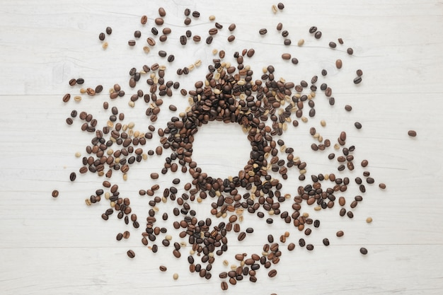 Erhöhte ansicht von rohen und gerösteten kaffeebohnen auf hölzernem schreibtisch