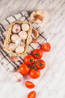 Erhöhte ansicht von roten tomaten; zwiebeln; knoblauchzehen und tuch auf marmoroberfläche