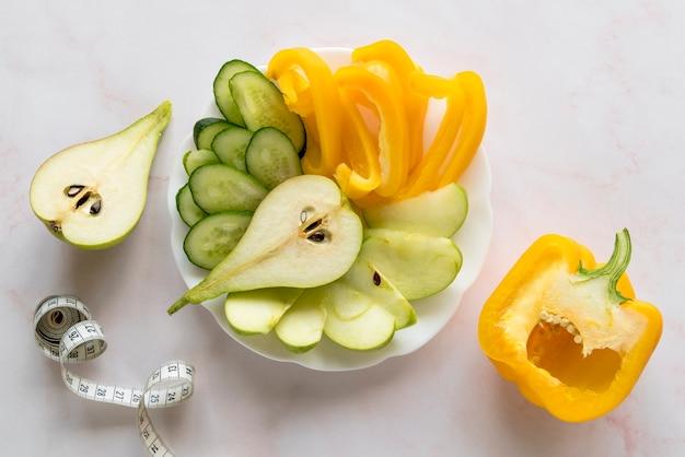 Erhöhte ansicht von scheiben des gemüses und der früchte mit maß