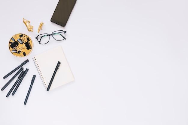 Erhöhte ansicht von schreibwaren und von brillen auf weißem hintergrund