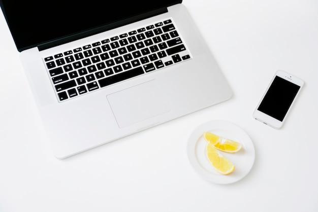 Erhöhte ansicht von süßer limone; smartphone und laptop auf weißem hintergrund