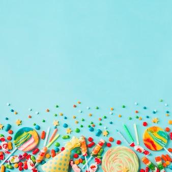 Erhöhte ansicht von süßigkeiten; partyhut und kerzen auf blauem hintergrund