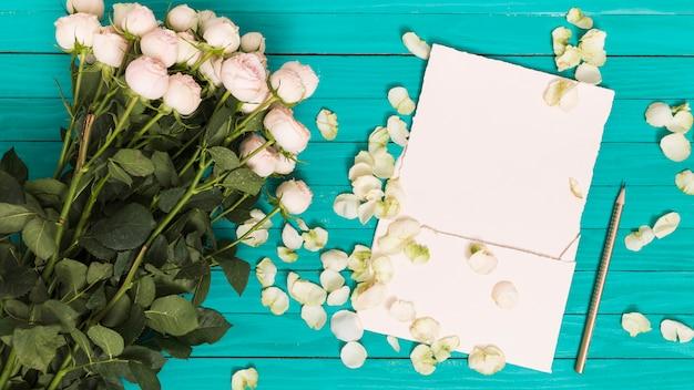 Erhöhte ansicht von weißen rosen; bleistift; leeres blatt; und blütenblätter gegen grünen holztisch