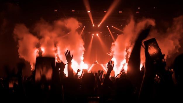 Erhöhte hände silhouetten in einem musikkonzert oder festival