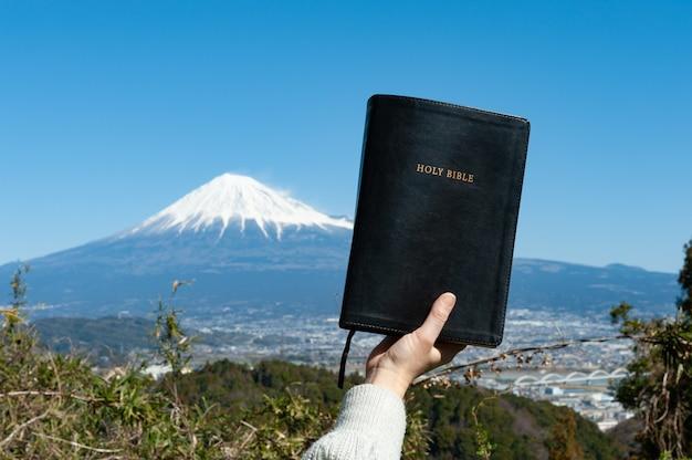 Erhöhte hand, die die heilige bibel vor dem berg fuji in japan hält