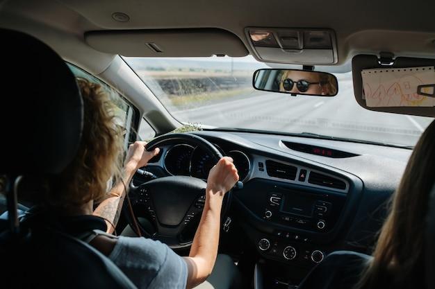 Erhöhte rücksitzansicht einer frau, die ihr auto fährt. hoher winkel. sie trägt eine sonnenbrille, ihr gesicht spiegelt sich in einem spiegel.