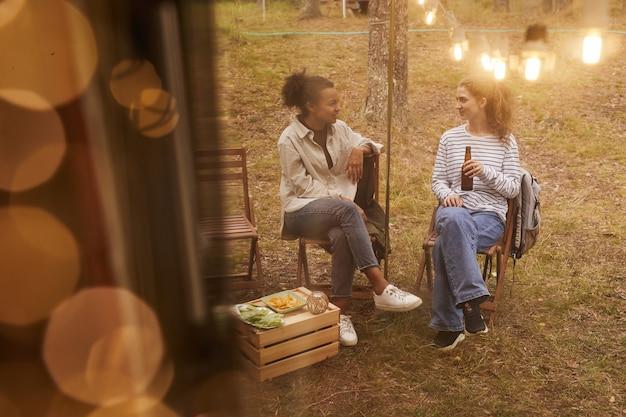 Erhöhte sicht auf zwei junge frauen, die sich beim camping im freien mit einem von lichterketten beleuchteten van entspannen ...