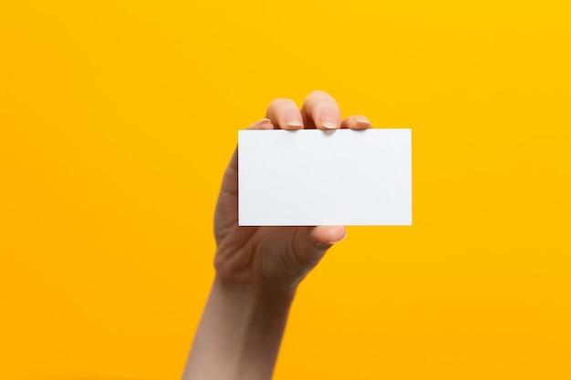 Erhöhte weibliche hand mit einer weißen karte. attrappe, lehrmodell, simulation. gelber hintergrund. speicherplatz kopieren.