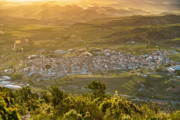 Erhöhten blick auf eine stadt zur goldenen stunde, umgeben von weinbergen la font de la figuera valencia spain
