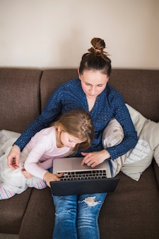 Erhöhte Ansicht der Frau sitzend mit ihrer Tochter, die an Laptop arbeitet