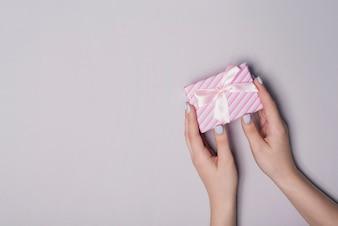 Erhöhte Ansicht der Hand Geschenkbox gegen grauen Hintergrund halten
