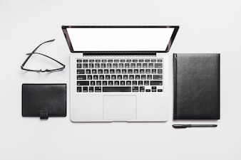 Erhöhte Ansicht des Laptops; Schauspiele und Tagebücher auf weißem Hintergrund