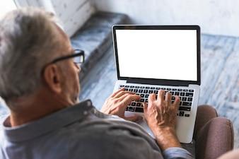 Erhöhte Ansicht des Mannes, der Laptop mit weißem leerem Bildschirm verwendet