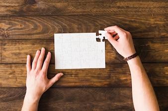 Erhöhte Ansicht des Mannes Puzzlespiel über Holztisch lösend