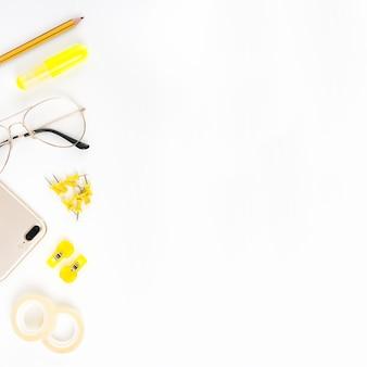 Erhöhte Ansicht des Mobiltelefons; Brillen und Schreibwaren auf weißem Hintergrund