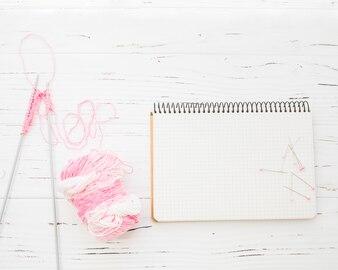 Erhöhte Ansicht von Häkeln; Garn; Notizblock und nähende Stifte vom hölzernen Hintergrund