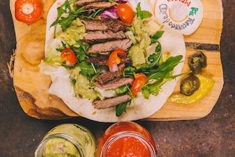 Erhöhte Ansicht von mexikanischen Tacos mit Rindfleisch auf Schneidebrett mit Gläsern Guacamole und Salsasoße