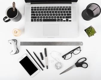 Erhöhte Ansicht von schwarzem Kaffee; Laptop; Handy und Schreibwaren auf weißem Hintergrund