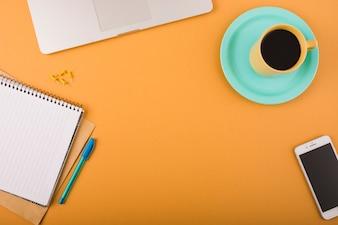 Erhöhte Ansicht von schwarzem Kaffee; Smartphone; Stift; Drucknadeln; Laptop und Notizblock auf orange Hintergrund