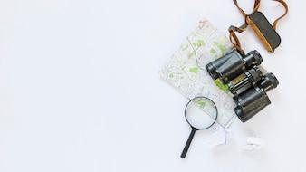Erhöhte Ansicht von zerknittertem Seidenpapier; Karte; Fernglas und Lupe auf weißem Hintergrund