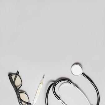 Erhöhte Sicht von Brillen; Stethoskop und Thermometer auf grauem Hintergrund