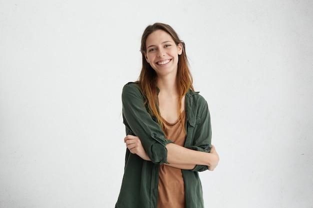 Erholsame frau mit gefärbtem haar, die gekreuzte hände steht und ein aufrichtiges und entzückendes lächeln zeigt, das ihre perfekte zahnaufstellung demonstriert