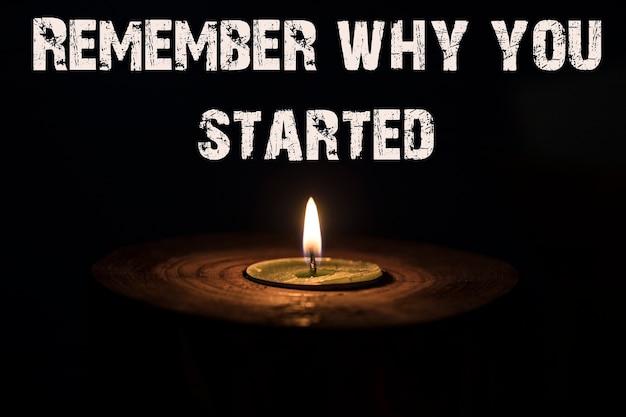Erinnern sie sich, warum sie angefangen haben - weiße kerze mit dunklem hintergrund - in einem hölzernen kerzenständer.