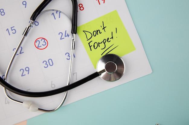 Erinnerung auf eine haftnotiz in einem kalender geschrieben, um einen arzt aufzusuchen.