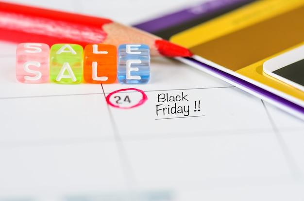 Erinnerung black friday sale im weißen kalender mit rotem stift und kreditkarten