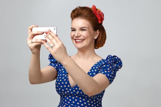 Erinnerungen sammeln. porträt der schönen eleganten jungen kaukasischen frau, die rotes stirnband und gepunktetes weinlesekleid trägt, das fröhlich lächelt, während sie selfie nimmt