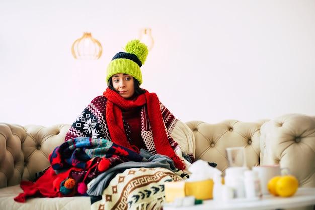 Erkältet. süße junge kranke frau fühlt sich kalt und krank, sitzt auf einer couch und ist warm gekleidet in einem pullover, einem schal und einer grünen strickmütze.