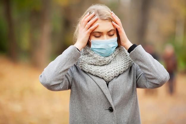 Erkältung und grippe. frau mit einer medizinischen gesichtsmaske an im freien