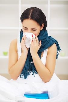 Erkältung und grippe. porträt der kranken frau, die kalt erwischt wird, sich krank fühlt und im papiertuch niest. nahaufnahme der schönen ungesunden frau bedeckt in der decke, die nase wischt. gesundheitskonzept. hohe auflösung