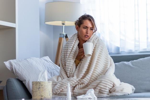Erkältung und grippe. porträt der kranken frau, die kalt erwischt wird, sich krank fühlt und im papiertuch niest. nahaufnahme des schönen ungesunden mädchens bedeckt in der decke, die nase wischt. gesundheitskonzept.